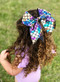 """Mermaid cheer bow in metallic rainbow fish scale pattern. Approximately 6"""" across with 6"""" tails."""
