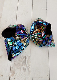 "A Texas sized alligator clip bow in metallic rainbow fish scale pattern. Approximately 7""+ inches across."
