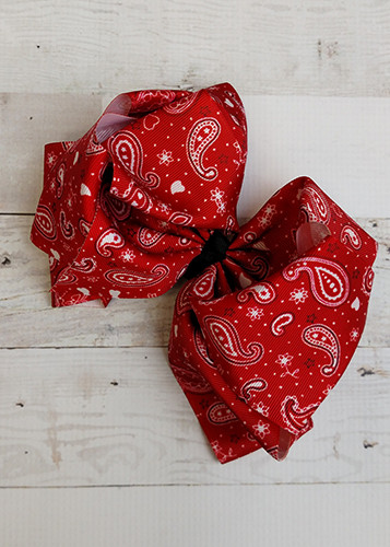 """A large double looped grosgrain ribbon hair bow in a fun red bandana print.  Attaches with a large 3"""" alligator clip with """"teeth"""" for a secure hold.  The bow measures approximately 6.5"""" long and 5"""" wide."""
