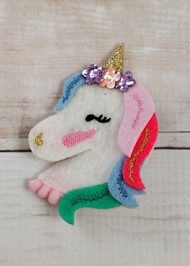 Felt unicorn hair clip with glitter accents and alligator clip backing.