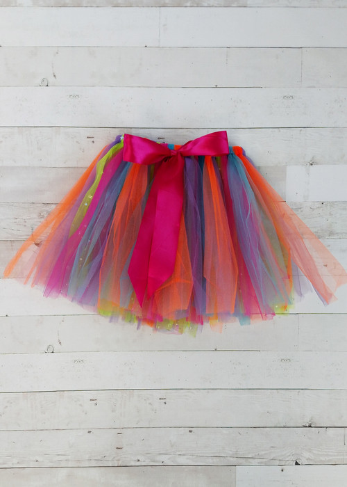 Rainbow sparkle tie tutu featuring assorted colors of glitter tulle looped over an elastic waistband with a hot pink bow accent.