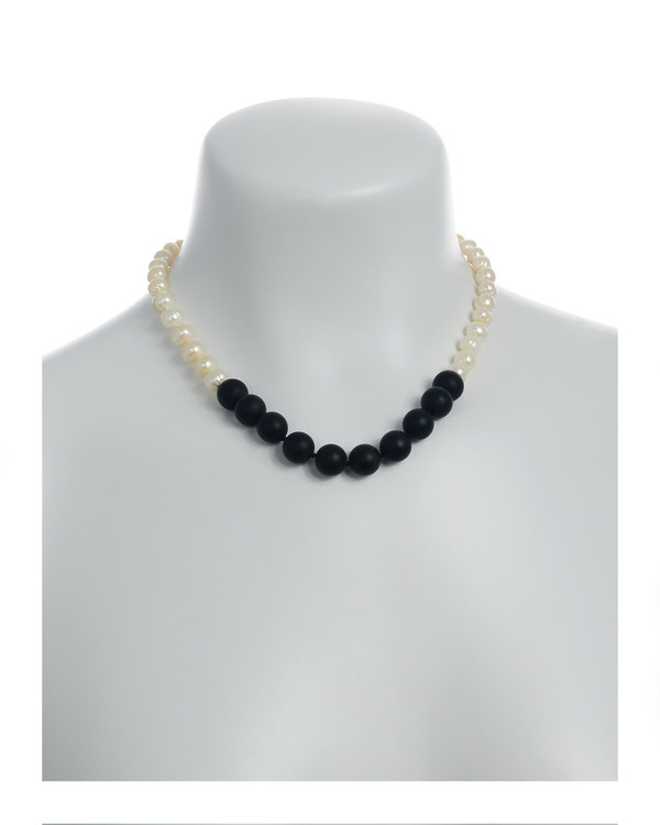 Copacabana Promenade II - Pearl Necklace with Onyx On model: Single strand graduated white freshwater pearls 6-10mm, leading to untumbled onyx beads 12mm, on individually hand knotted natural silk, with rare earth mixed metal clasp