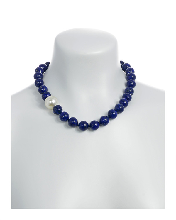 Côte d'Azur - Lapis and Pearl Necklace On model: Single strand lapis beads 14mm flecked with pyrite, with offset shell pearl 20mm, on individually hand knotted black silk, featuring rare earth mixed metal magnetic clasp
