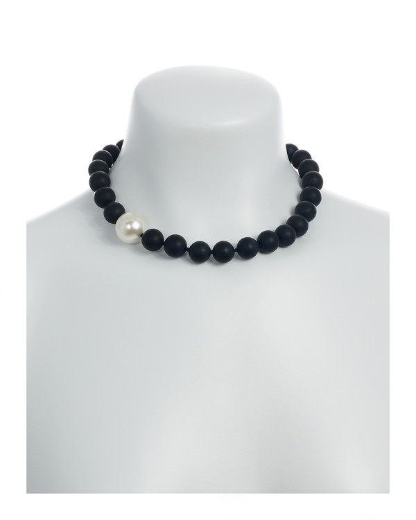 on model: London Eye Pearl and Onyx Necklace: Single strand black untumbled onyx beads 14mm, featuring an offset single shell pearl 20mm, on individually hand-knotted black silk, with rare earth magnetic mixed metal clasp