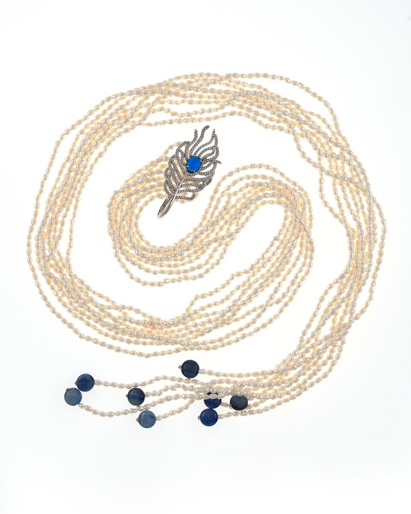 "Catedral de Mármol - Pearl Necklace, 8-strands of white seed pearls, 3-4mm, individually hand-knotted on natural silk, finished with 8 kyolite beads at the ends and held together with a mixed-metal feather pendant hand set with CZ's at 32"" in length."