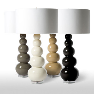 As Shown: Mulholland Table Lamp Size: 18 diameter x 32 H inches Material: Glazed Porcelain Color: Off-White, Grey, Beige, Black Shade: Silk Shade Color: Of-White  Description: Stacked globes proceed from large to small up this sculptural, glazed porcelain table lamp, available in four colors. Fitted with a white silk drum shade with gold lining, the Mulholland Table Lamp speaks fluent, curated luxury.