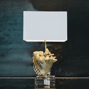 As Shown: See Worthy Shell Lamp Size: 8 x 12 x 21 H inches Material: Conch Shell on Acrylic Base Shade: Linen  Description: Be transported to the Bahamas with a sophisticated mix of materials, finishes, and shapes in a glamorously organic piece. Crafted by hand, a gold metallic-painted conch shell is attached to an acrylic base with antique bronze hardware, then topped with a white opaque shade. A pair on night tables; part of a vignette with books and artwork in an entry; for drama on a living room side table.