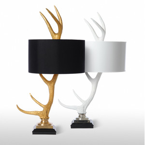 As Shown: Breckenridge Table Lamp Size: 18 diameter x 39 H inches Material: Ceramic Composite Color: Gold, White Shade: Silk, Painted Parchment  Description: These table lamps bring some of the drama of the rustic to sculpted ceramic composite, artfully updated by black or white drum shades and black bases. The layered elements balance like the horns on a deer's head.
