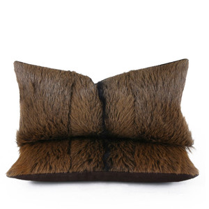 As Shown: Country Goat Pillow Size: 9 x 18 inches Material: Goat Hide  Color: Brown Description: Colorations of chestnut brown and black goat hide with a black center stripe make for a handsome lumbar pillow. By hand artisans seam the hides in three sections then back in brown linen. Fitted with a feather and down inner, your pillow will be individually created for you. Each of these furry hides varies for a singular piece that is unique to you.  We love lining a pair up on a sofa or bed for a warm glow.
