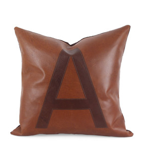 As Shown: To The Letter Pillow Size: 18 x 18 inches Material: Leather Color: Saddle Brown with Chocolate Brown Letter  Description: Celebrate your favorite letter – or word – with these graphic leather pillows. By hand artisans cut and attach the letter to the leather surface below with a topstitch outline then back with matching linen or leather. Fitted with a feather and down inner, your pillow will be individually created for you. Line up a few in a media or game room for family members' initials or to spell words: PLAY, SING, FILM, GAME, LOVE, whatever you WISH.