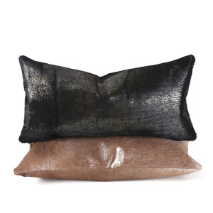 As Shown: Vail Metallic Hide Pillow Size: 9 x 18 inches Material: Cowhide  Color: Black, Golden Brown Description: A stunning juxtaposition of cool metallic modernity and warm natural cowhide occurs when gold foil is applied to a hide.  Artisans hand-foil the hair-on cowhide front and matching back then fit with a feather and down inner. Your pillow will be individually created for you. Adding unexpected gloss to a classic western material ensures you a sophisticated piece in any setting.