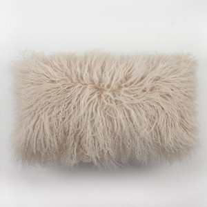 As Shown: Sand Dune Mongolian Lamb Pillow Size: 10 x 18 inches  Description: You'll love to cozy up with this pale sand Tibetan fur pillow. Its soft hue injects lush texture when tossed into any interior. By hand, artisans craft these premium designer-quality lambskin cushions. Backed in matching fabric with a feather and down inner, your pillow will be individually created for you.
