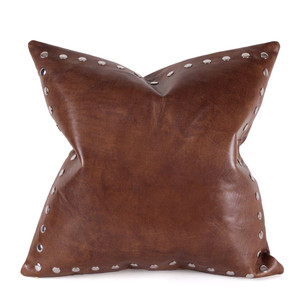 As Shown: Border Stud Pillow Size: 16 x 16 inches Material: Leather Color: Saddle Brown  Description: Metal studs march around a wide open space enhancing the rich leather grain with their high-contrast sheen. Artisans attach flat silver studs by hand to the front then back with matching linen or leather. Fitted with a feather and down inner and hidden zipper, your pillow will be individually created for you. The sleek modern metal and classic clubby leathers make it a timeless addition to your cozy confines.