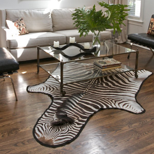 As Shown: Genuine Burchell Zebra Hide Rug Size: 11 to 15 sq ft (each is unique, please allow for variation) Material: Zebra Hide with Felt Back  Description: Ground your space with impactful natural contrast and be transported to the wild. Artisans select responsibly culled hide, then back in felt. Each rug is unique and averages 11-15 square feet; please allow for variation.