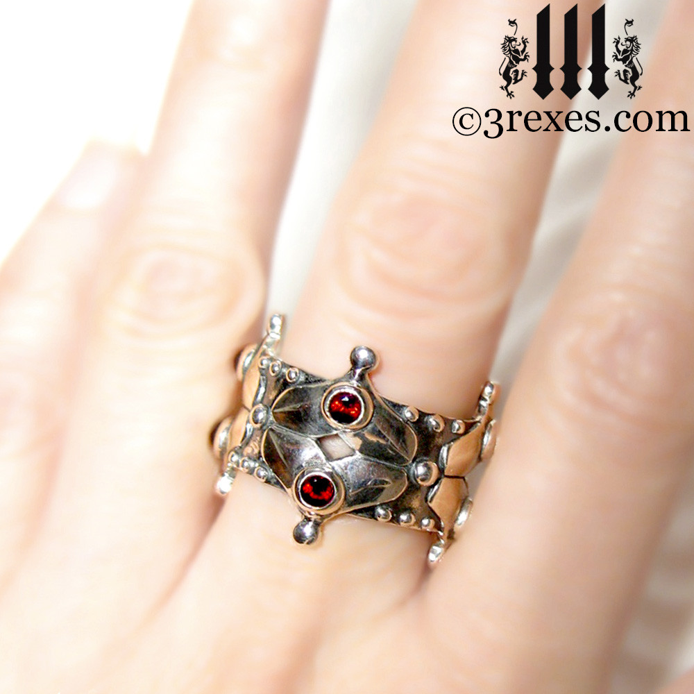 silver crown ring with faceted garnets on middle finger