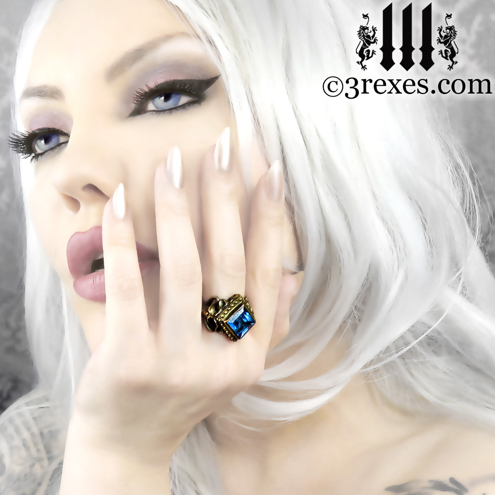 raven love brass wedding ring with large blue topaz stone Model: Elena V.