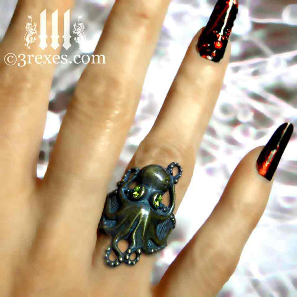 antiqued brass octopus ring with faceted green peridot eyes model view