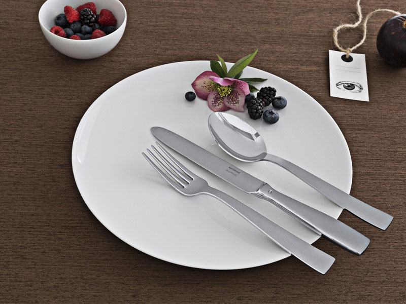 Sambonet flatware Gio Ponti fork, knife and spoon on white plate sitting on wooden table top.