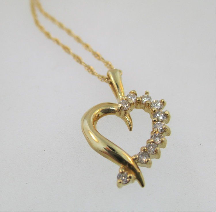 14k yellow gold heart shaped pendant with approx 25ct tw of 14k yellow gold heart shaped pendant with approx 25ct tw of diamonds accenting the aloadofball Choice Image